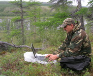 Jon Ranson working on an expedition blog post along the Kotuykan River in northern Siberia, July 2008.